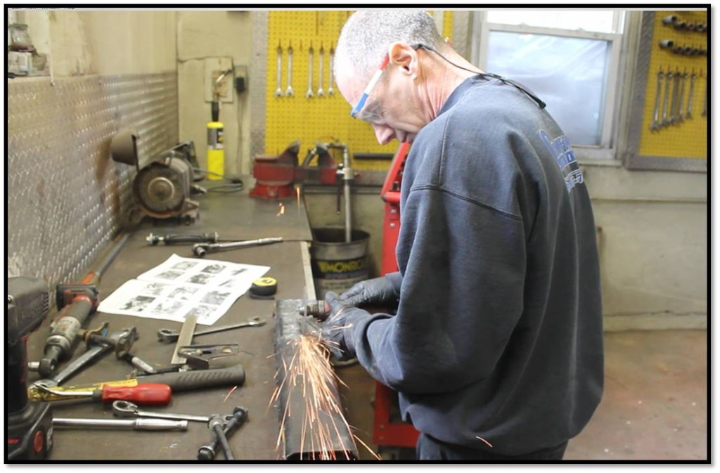 Vinny demonstrates proper use of safety eyewear while using the cutting wheel to clearance the factory front cross-member for the dropped diff.