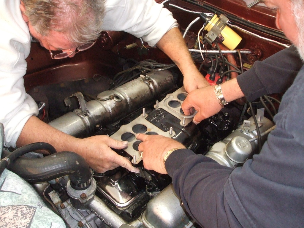 We carefully mate the manifold to the heads.  It's hard to lean over like that after a box of donuts.