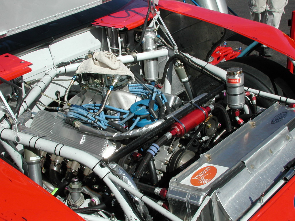 This image shows the hoses, tubing, external reservoir and a little of the dry sump pump of a NASCAR engine. The pump can be barely seen at the left of the image.