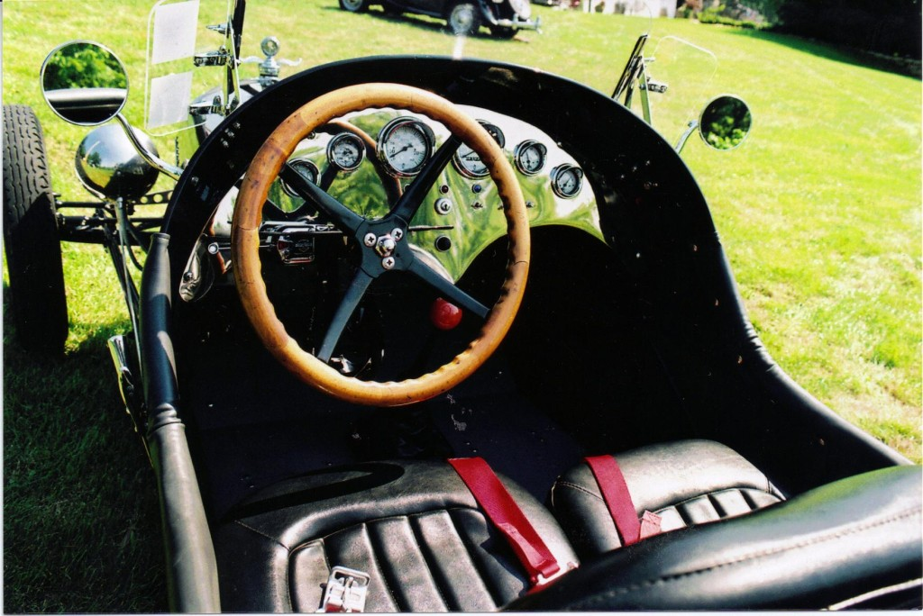 Adjustable black vinyl bucket seats have red seat belts and the four-spoke steering wheel is set in the right position for a driver of Kurt's stature.