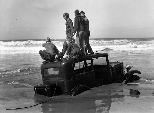 Boys perch atop an old car badly stuck in the surf on Nye Beach. Getting trapped in the sand by the tide has been a common peril of beach travel. (Lincoln County Historical Society, LCHS #32)