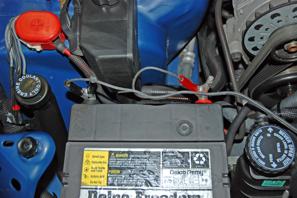 Both timing light power cables should be affixed to the battery. In the event that your race car has a trunk mount battery or pair of batteries, add a power junction block to an accessible location in the engine compartment. Never use the coil as a source of timing light power.