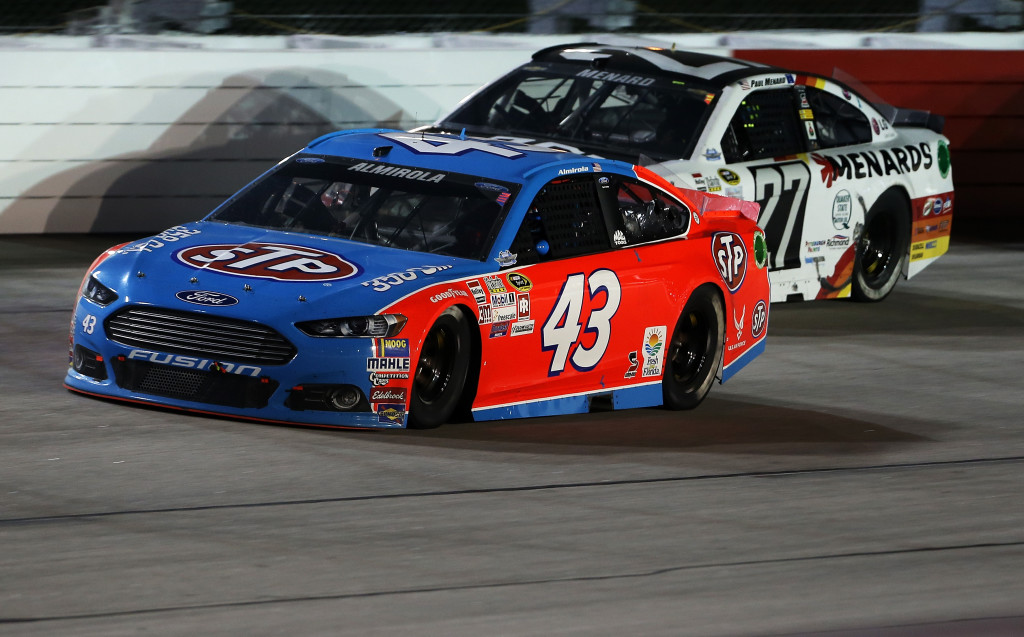Aric Almirola, driver of the #43 STP Ford, races Paul Menard, driver of the #27 Chevrolet, during the NASCAR Sprint Cup Series Bojangles' Southern 500 at Darlington Raceway.