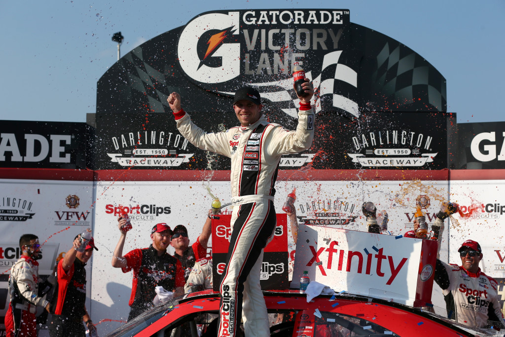 Denny Hamlin, driver of the #20 Sport Clips Toyota, celebrates in Victory Lane after winning the NASCAR XFINITY Series VFW Sport Clips Help A Hero 200