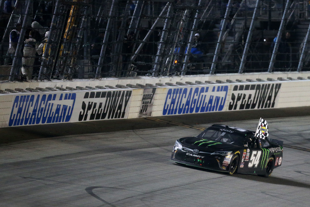 Kyle Busch, driver of the #54 Monster Energy Toyota, celebrates with the checkered flag after wining the NASCAR XFINITY Series FURIOUS 7 300 at Chicagoland Speedway