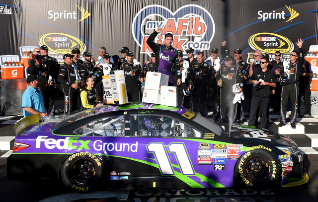 Denny Hamlin, driver of the #11 FedEx Ground Toyota, celebrates in Victory Lane after winning the NASCAR Sprint Cup Series myAFibRisk.com 400 at Chicagoland Speedway