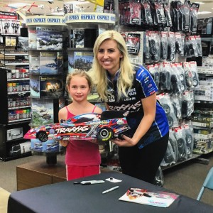 Courtney Force takes a photo with a young fan at Hobby Bench on Thursday before the race weekend on behalf of Traxxas.