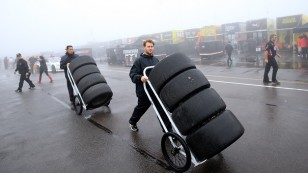 "LONG POND, PA - JUNE 05:  Crew members push tires through the garage area during the NASCAR Sprint Cup Series Axalta ""We Paint Winners"" 400 at Pocono Raceway on June 5, 2016 in Long Pond, Pennsylvania.  (Photo by Chris Trotman/NASCAR via Getty Images)"