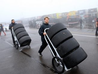 """LONG POND, PA - JUNE 05:  Crew members push tires through the garage area during the NASCAR Sprint Cup Series Axalta """"We Paint Winners"""" 400 at Pocono Raceway on June 5, 2016 in Long Pond, Pennsylvania.  (Photo by Chris Trotman/NASCAR via Getty Images)"""