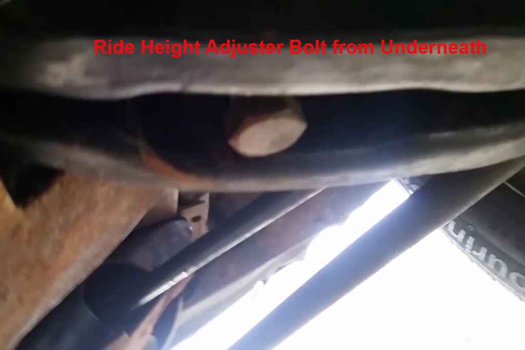 The ride height adjuster bolt as seen from under the car. Image from screenshot.