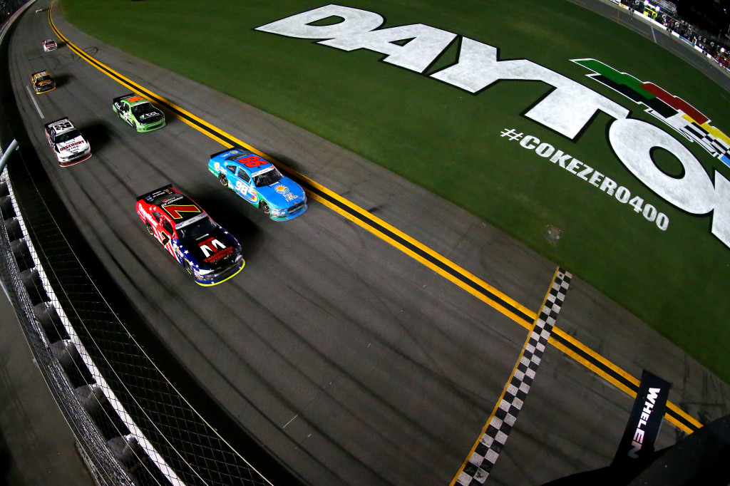 DAYTONA BEACH, FL - JULY 01:  Aric Almirola, driver of the #98 Fresh From Florida Ford, leads Justin Allgaier, driver of the #7 TradeMark Nitrogen Chevrolet, and the rest of the field to the checkered flag under caution to win the NASCAR XFINITY Series Subway Firecracker 250 at Daytona International Speedway on July 1, 2016 in Daytona Beach, Florida.  (Photo by Sarah Crabill/NASCAR via Getty Images)