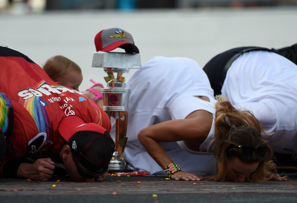 INDIANAPOLIS, IN - JULY 24:  Kyle Busch, driver of the #18 Skittles Toyota, kisses the bricks with his wife, Samantha, and son, Brexton, after winning the NASCAR Sprint Cup Series Crown Royal Presents the Combat Wounded Coalition 400 at Indianapolis Motor Speedway on July 24, 2016 in Indianapolis, Indiana.  (Photo by Bobby Ellis/Getty Images)