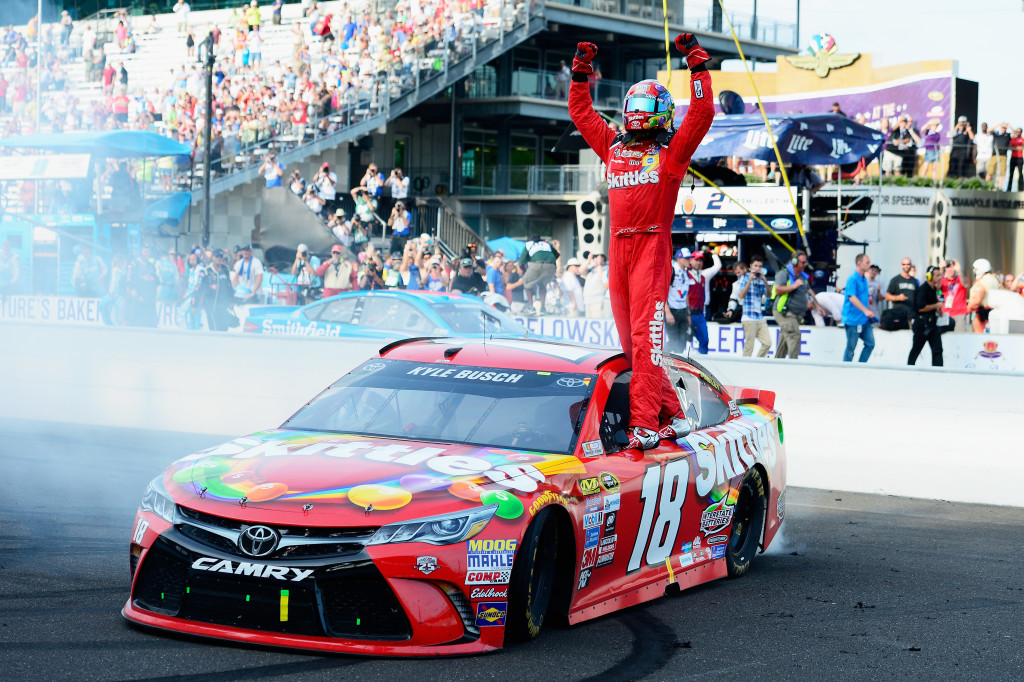 INDIANAPOLIS, IN - JULY 24:  Kyle Busch, driver of the #18 Skittles Toyota, celebrates winning the NASCAR Sprint Cup Series Crown Royal Presents the Combat Wounded Coalition 400 at Indianapolis Motor Speedway on July 24, 2016 in Indianapolis, Indiana.  (Photo by Robert Laberge/Getty Images)