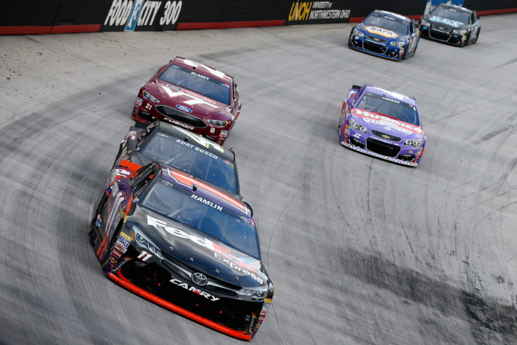 BRISTOL, TN - AUGUST 21: Denny Hamlin, driver of the #11 FedEx Express Toyota, leads a pack of cars during the NASCAR Sprint Cup Series Bass Pro Shops NRA Night Race at Bristol Motor Speedway on August 21, 2016 in Bristol, Tennessee. The race was delayed due to inclement weather on Saturday, August 20. (Photo by Brian Lawdermilk/Getty Images)