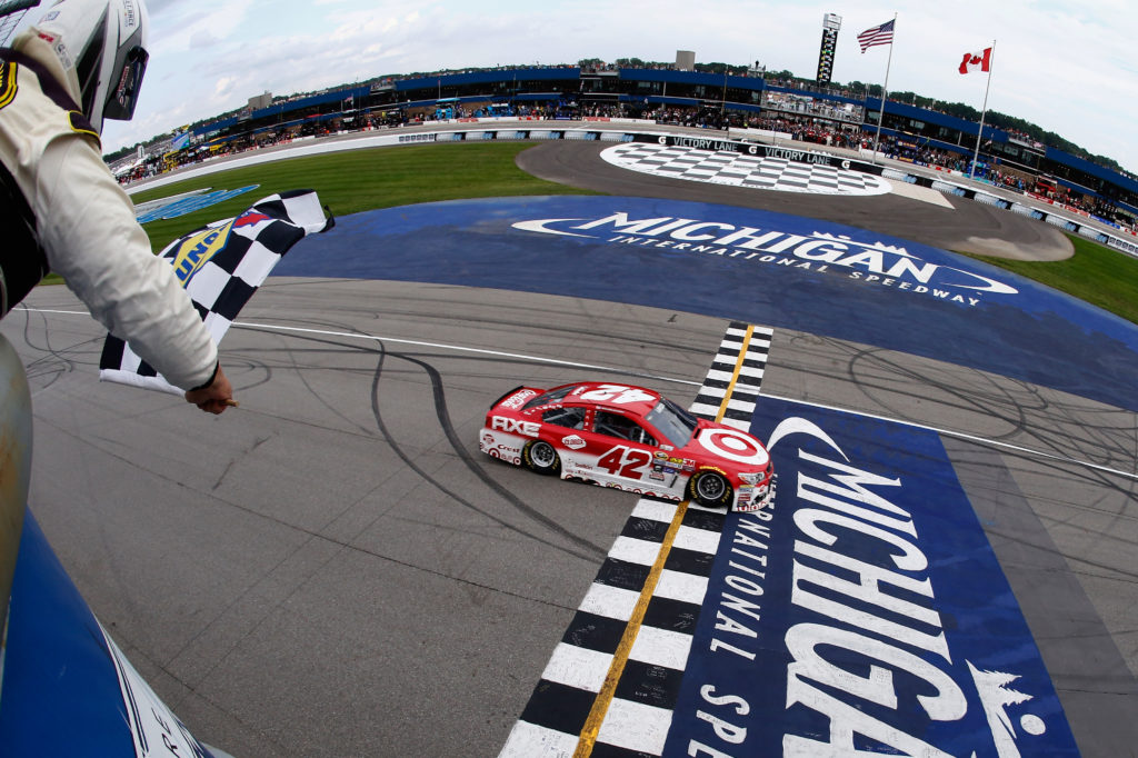 BROOKLYN, MI - AUGUST 28:  Kyle Larson, driver of the #42 Target Chevrolet, takes the checkered flag to win the NASCAR Sprint Cup Series Pure Michigan 400 at Michigan International Speedway on August 28, 2016 in Brooklyn, Michigan.  (Photo by Jeff Zelevansky/NASCAR via Getty Images)