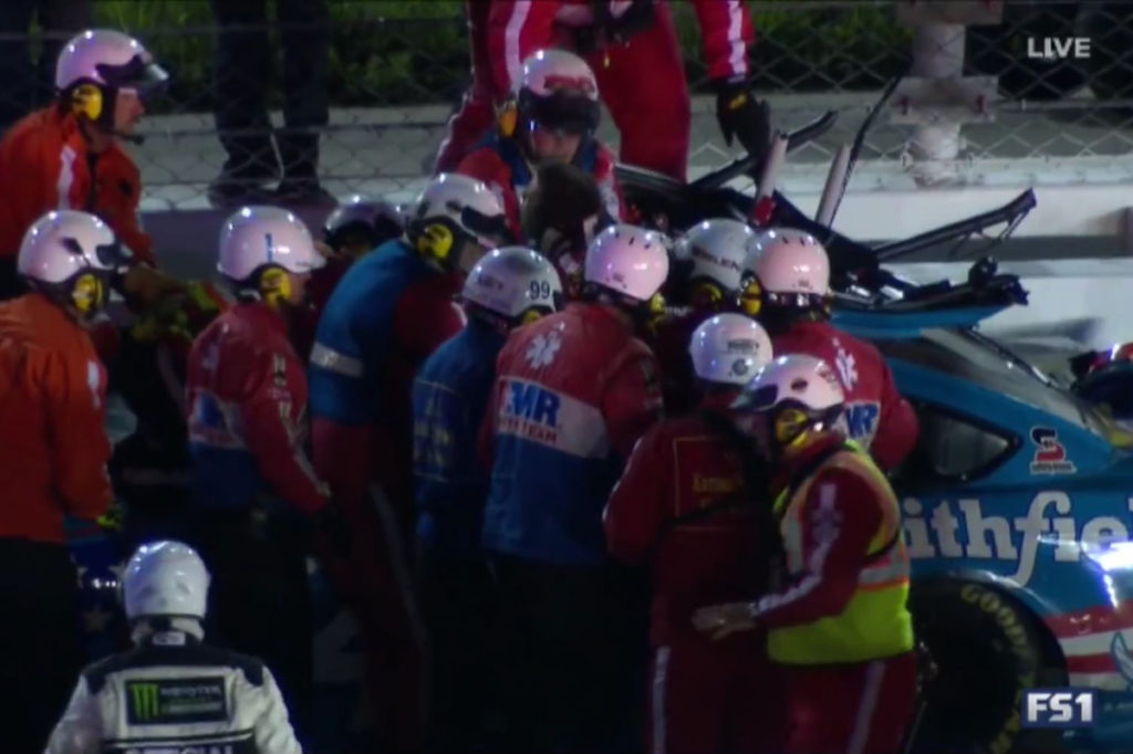 After peeling half of the top of the car back, safety workers strap Almirola to a backboard and lift him up and out of the car.