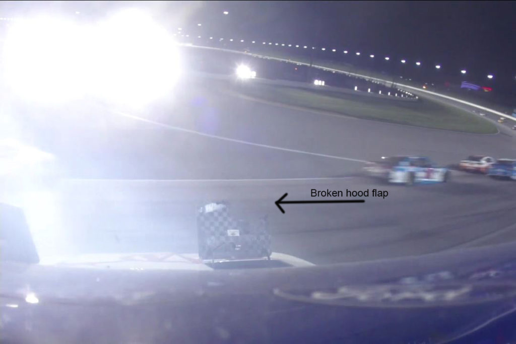 This image shows that the corner one of the hood flaps on Logano's car has clearly been shattered by something